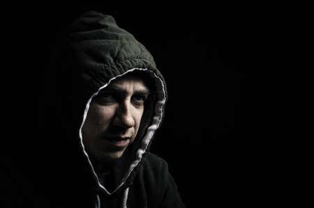 merciless: Hooded thug staring