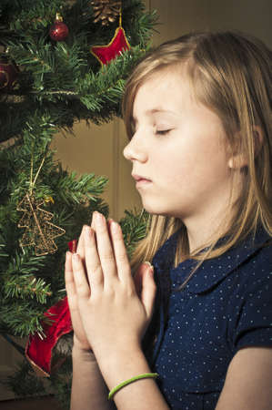 Child praying at christmas
