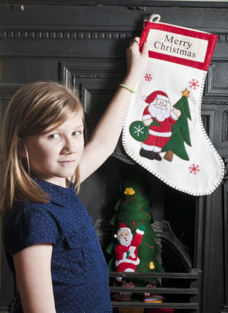victorian fireplace: Girl hanging her christmas stocking Stock Photo