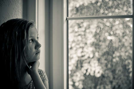 Worried girl at the window photo