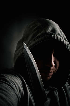 Hooded thug holding a knife photo