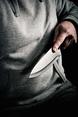 Thug holding a knife and thrusting it forward photo