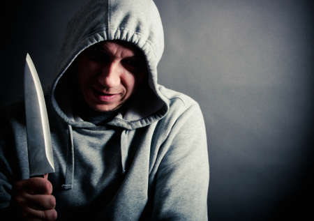 holding a knife: Evil gang member holding a knife