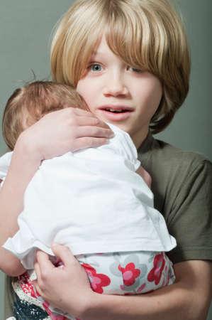 lovingly: Boy lovingly holding a new born baby Stock Photo