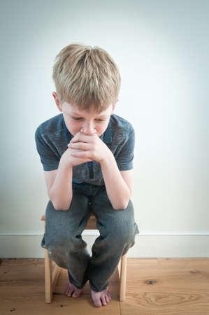 Frightened boy sat alone