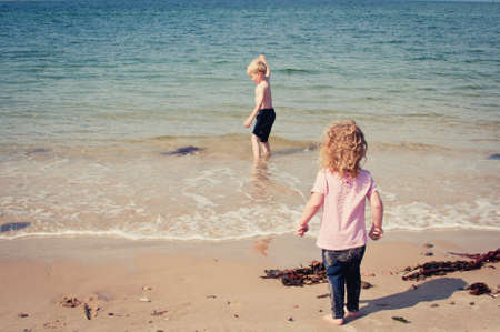 Little girl watching her older brother playing in the sea