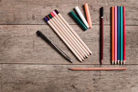 pallette: An artists coloured pencils seen from above against a textured wooden background Stock Photo