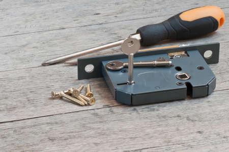 Türschloss und Schlüssel mit Schlosser Tool gesehen gegen einen strukturierten Hintergrund aus Holz Standard-Bild - 72437565