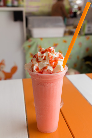 sweet strawberry milkshake and frappe - iced and milk blended with whiping creams photo