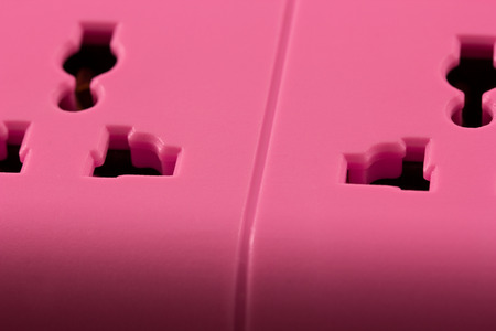 alternating current: Closeup picture of a pink outlet isolated on black  Electric Power Line on balck background