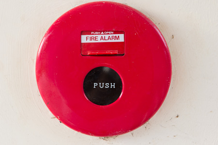 Dirty fire alarm on the wall of the building photo