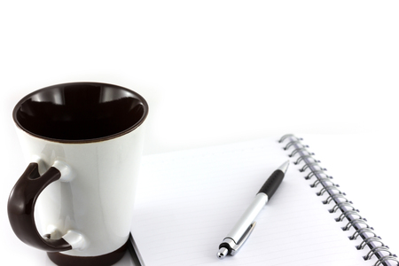 Cup of coffee and notebook isolate on white background photo