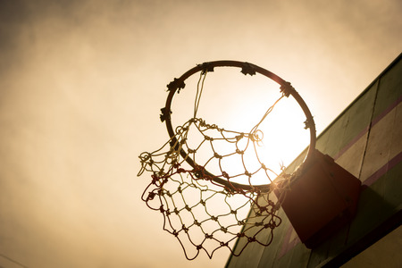 Wooden basketball hoop during sunset. photo