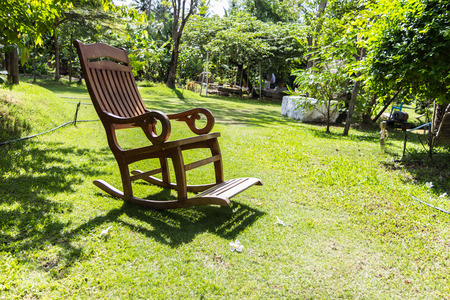 Empty rocking chair over grass at summer sunset photo