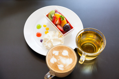 strawberry cream and a cup of tea and cofee on a wooden background, selective focus photo