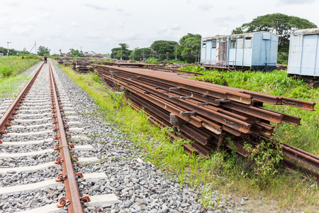 cross ties: Overview of a railroad track and piles of cross ties lying along it on the sides Stock Photo