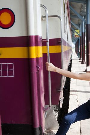 enters: Woman enters train holding the rail