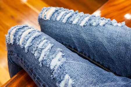 fragmentary: leg of women in fragmentary and torn jeans background