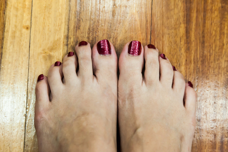 women feet after pedicure with red nails background photo