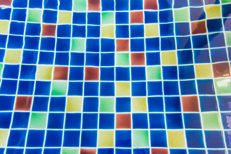 Sun reflection on the blue clear water ripples of swimming pool with mosaic bottom photo