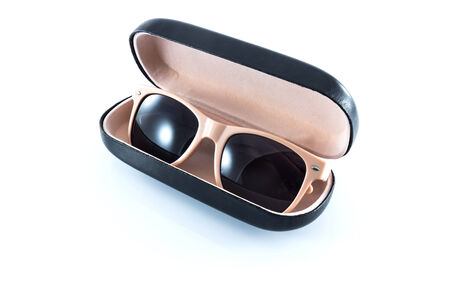 pink sunglasses in pink opened case on white background  photo