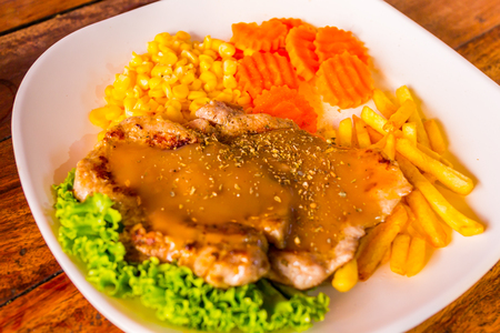 Grilled pork steak, French fries and vegetables photo
