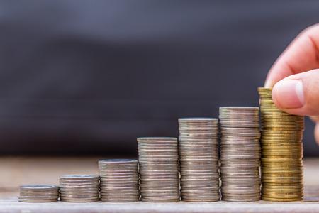 お金、金融、ビジネスの成長概念、ハンド数、置くお金をスタックのコインのクローズ アップ