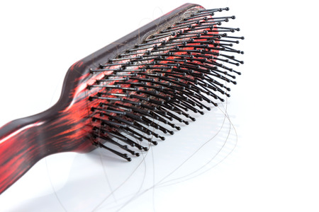 pelade: Comb and hair on white background