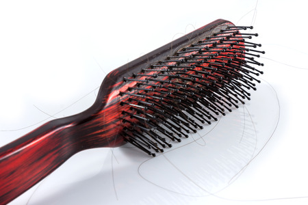 Comb and hair on white background
