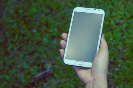 Closeup of female hands using a smart phone, green nature background photo