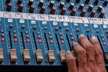 Audio mixing console closeup with hand photo