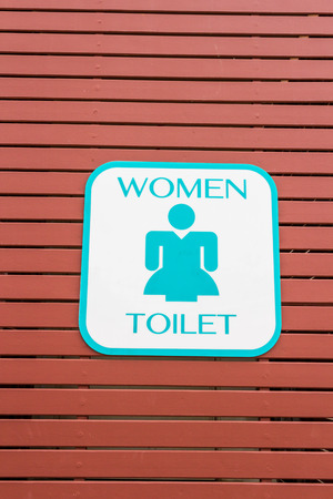 toilet signs of woman on brow wood photo