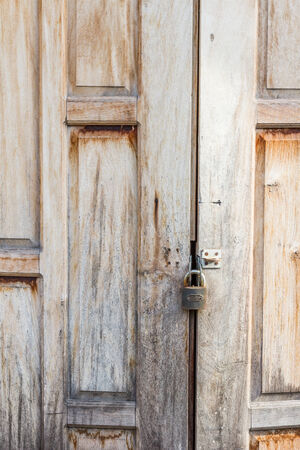 Old weathered wooden door made from planks. With  lock photo