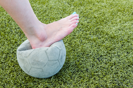 underdeveloped: Girl Barefoot and old soccer ball background Stock Photo