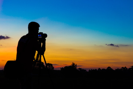夕日を背景にシルエット写真家 写真素材