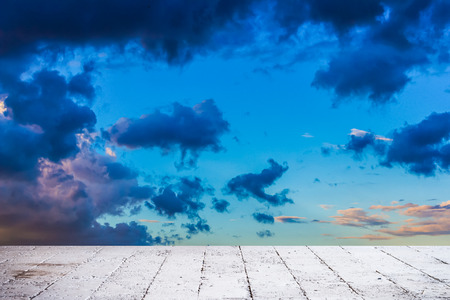 stratus: Dainty wispy pale salmon pink and golden yellow clouds at sunset  background with cement floor