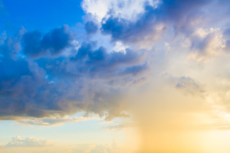 greys: Dainty wispy pale salmon pink and golden yellow clouds at sunset and raining background Stock Photo