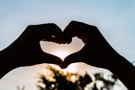 love shape hand silhouette at sunset background photo