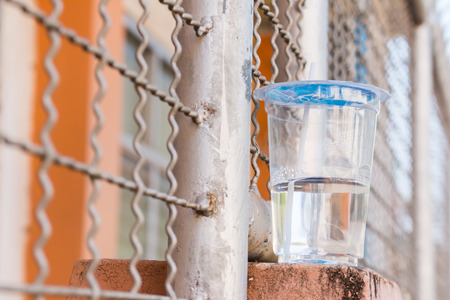 hand rails: Plastic cups with water on the wall of fence or barrier made of rails