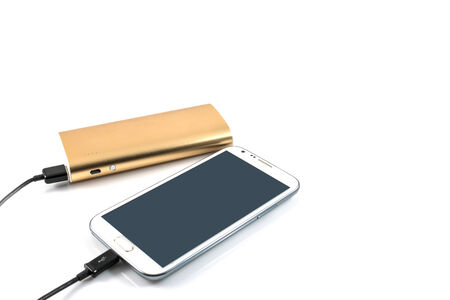 Gold power bank charging white smart phone on white