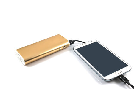 Gold power bank charging white smart phone on white  photo