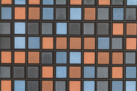 mosaic tile of a wall decorated with black blue gray and orange pattern tiles blackground photo