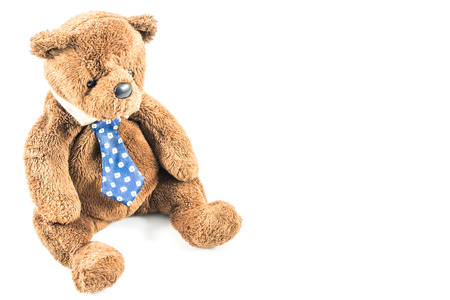 Old brown teddy bear with necktie on white background Stock Photo