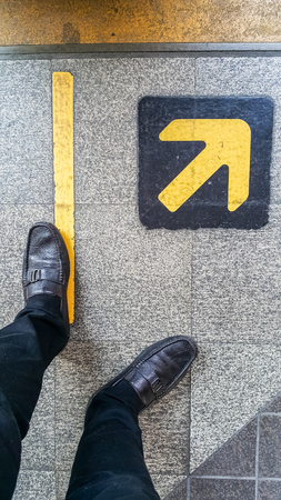 complete crossing: feet standing behind of the edge of a yellow line and yellow arrow on the stone floor