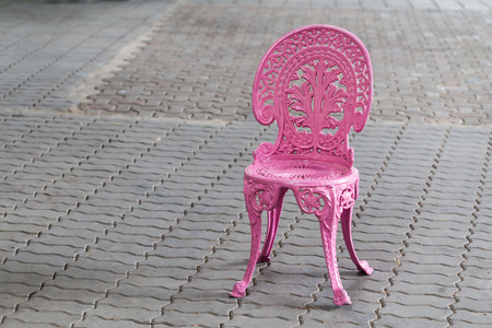 brick floor: Silla de la vendimia del metal rosado en el piso de ladrillo