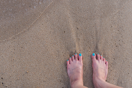 painted toenails: wave comes in to me, as I stand on the sand and wait at the beach. top down view