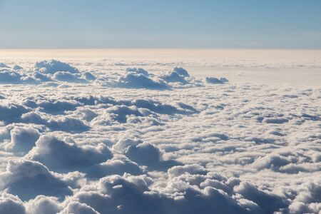 Fluffy white clouds and blue sky seen from airplane for background Stock Photo
