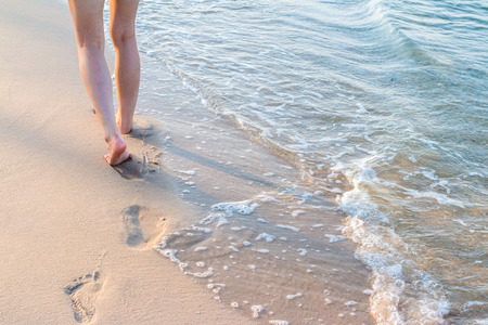 Lonely girl walking on the sand with footprints with wave Stock Photo
