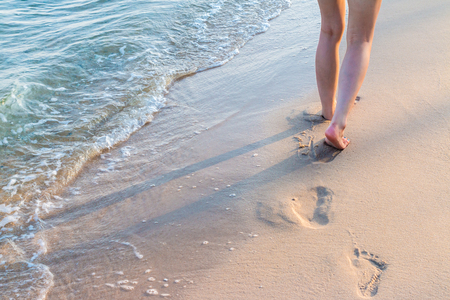 footprint sand: Lonely girl walking on the sand with footprints with wave Stock Photo