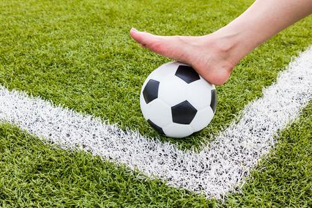 pies sexis: Mujer de pies descalzos en balón de fútbol para el fondo